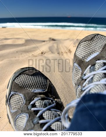 Crossed legs of woman relaxing on sandy beach casual young person wearing sneakers sitting by the sea selective focus. Closeup of crossed legs of woman resting at the sea.