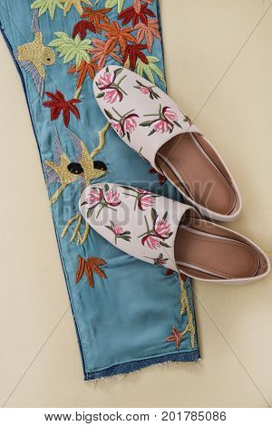 denim embroidered flowers,bird leg jeans texture.with shoes on khaki background