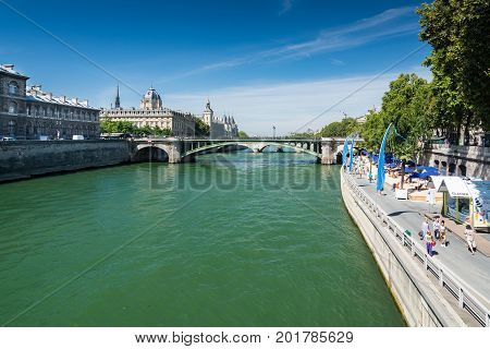 Paris France - August 13 2016: Tourists walking near The Seine in Paris. The Seine is an important commercial waterway within the Paris Basin in the north of France. In the background the Conciergerie.