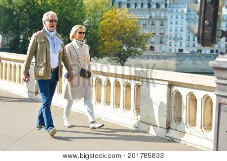 PARIS, FRANCE - OCTOBER 16, 2016: An elderly well dressed couple is walking and holding hands in a Paris, France.