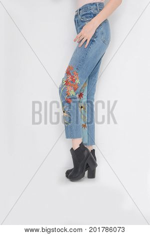 Fashion. Woman legs in Embroidered flowers, bird jeans with high heels shoes casual style isolated on white background