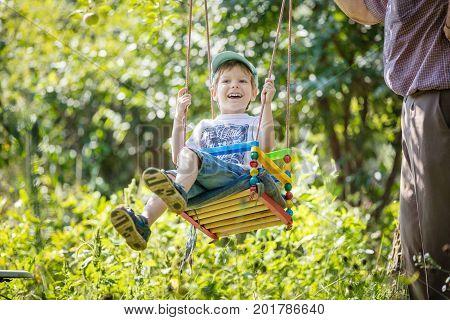 Senior man pushing laughing grandson on swing in garden