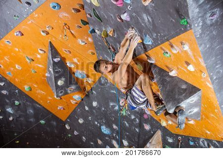 Young male rock climber on challenging route in indoor climbing gym