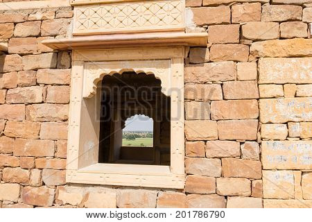 JAISALMER RAJASTHAN INDIA - MARCH 07 2016: Horizontal picture of sandstone bricks with beautiful window at the Thar Desert close to Jaisalmer in India.
