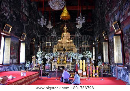 Bangkok Thailand - Aug 4 2017. People praying in Wat Arun temple. Wat Arun is a Monumental Buddhist temple right on the river with an iconic ornately tiled central prang (spire).