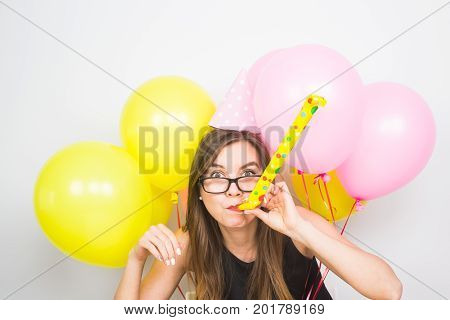 Young woman with party hat with noisemaker on a white background.