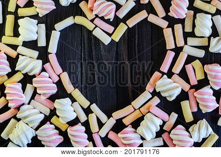 Laid out in the shape of heart multicolored marshmallows on black wooden table top view. Background of multi-colored and different in shape and size of marshmallows. Sweets background