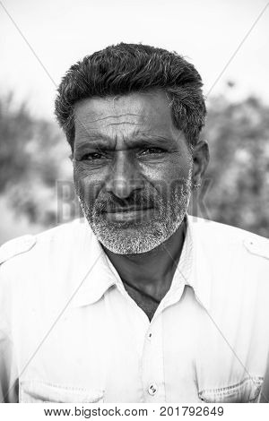 JAISALMER RAJASTHAN INDIA - MARCH 07 2016: Vertical black and white picture of native indian man in Thar Desert located close to Jaisalmer the Golden City in India.