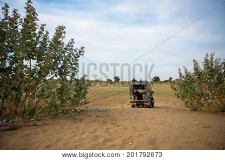 JAISALMER RAJASTHAN INDIA - MARCH 07 2016: Horizontal picture of green car parked in Thar Desert located close to Jaisalmer the Golden City in India.