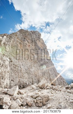 Female rock climber abseiling off climb during summer sunny day in Dolomite Alps, Cinque Torri, Italy - mountaineering, sport climbing or adventure concept