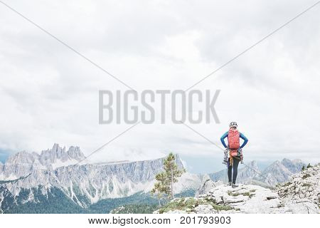 Female mountaineer with backpack, helmet and harness with climbing gear enjoying stunning view to mountains during summer day in Dolomite Alps - mountaineering, sport climbing or adventure concept