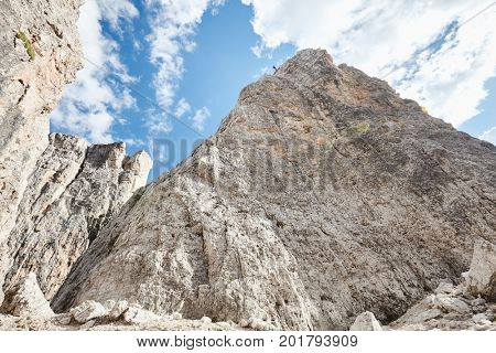 Female rock climber abseiling off climb during summer day in Dolomite Alps, Cinque Torri, Italy - mountaineering, sport climbing or adventure concept