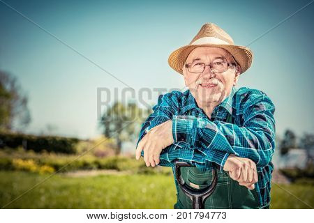 Portrait of a senior gardener standing in a garden with a shovel. Gardening