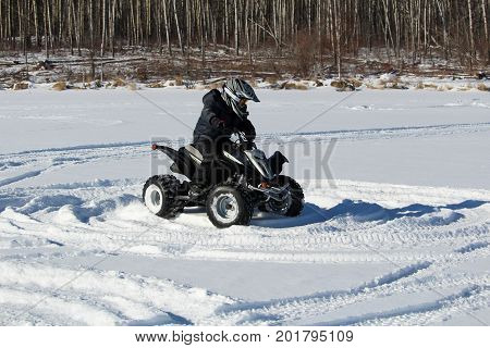 Child Driving A Quad In The Snow