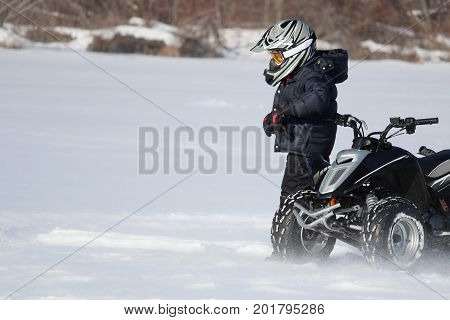 Child With His Quad in Winter with blowing snow around him