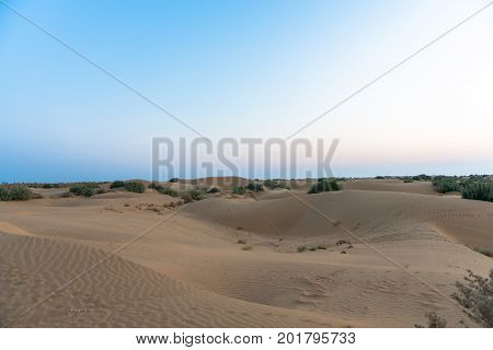 Panorama picture of sand dunes with colorful sky in Thar Desert located close to Jaisalmer the Golden City in India.