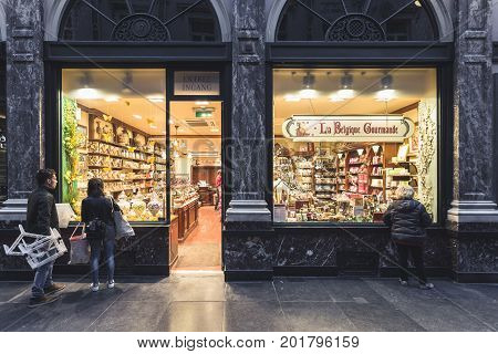 BRUSSELS BELGIUM - JUNE 18 2016: Horizontal picture of a chocolate store located inside the Galerie de La Reine with people looking into the store. Brussels.