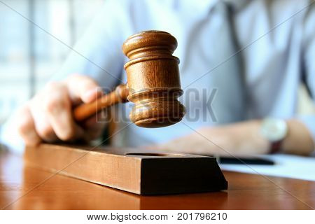 Judge holding gavel in courtroom. Profession. Violation