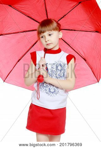A nice little blonde girl with a short bangs. In a red skirt and a white T-shirt with a pattern. The girl hid under the red umbrella.
