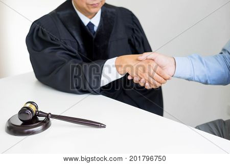 Gavel Hammer Justice On Wooden Table With Judge And Client Shaking Hands After Adviced In Background