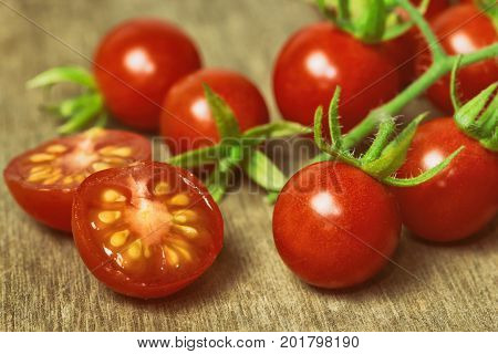 Fresh cherry tomato on rustic wood table. Close up lovely cherry tomato for background or wallpaper. Prepare fresh cut cherry tomato for home cooking look so delicious.Macro concept with copy space.Cherry tomato for fresh vegetable concept.