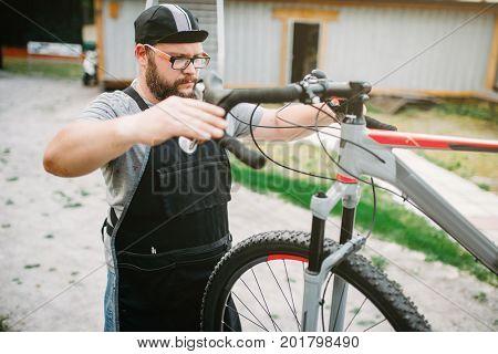 Mechanic adjusts the bicycle handlebars and brakes