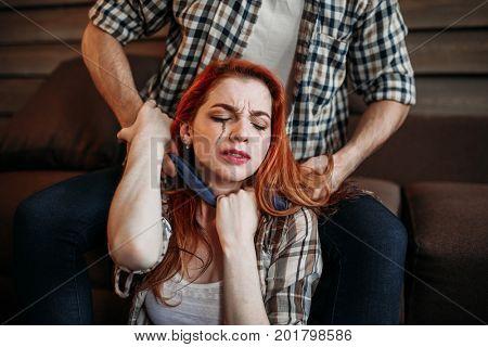 Male person strangles woman, domestic violence