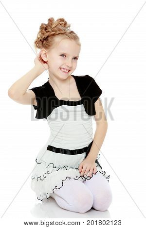 Beautiful little blonde girl dressed in a white short dress with black sleeves and a black belt.Girl stands on her knees and straightens her arm hair .Isolated on white background.