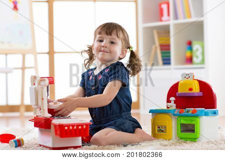 Child playing in nursery with educational toys. Toddler kid in playroom. Little girl cooking in toy kitchen.