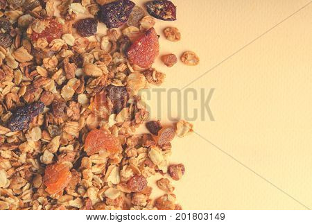 Homemade granola with honey, oatmeal, nuts, raisin, cranberry and dried apricots for background, top view, horizontal, toned with copy space