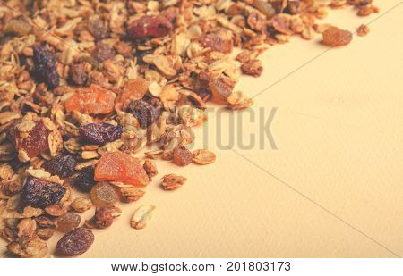 Homemade granola with honey, oatmeal, nuts, raisin, cranberry and dried apricots for background, top view, horizontal, toned