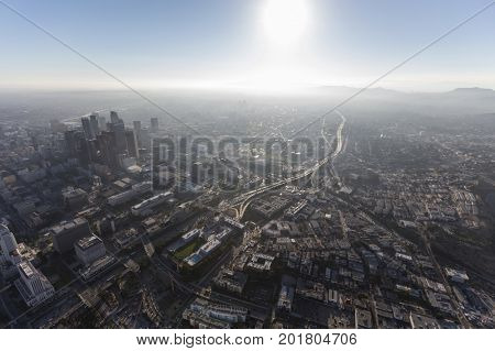Hazy summer afternoon aerial view of urban downtown Los Angeles streets and towers.