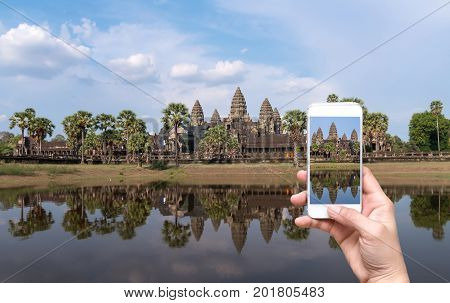 Female hands holding mobile smart phone taking pictures Angkor Wat at Siem Reap. Cambodia