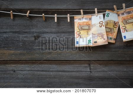 Money laundering concept -Euro banknotes hanging on clothesline on wooden background