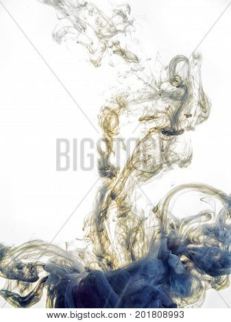 Ink swirl in water isolated on white background. The paint in the water. Soft dissemination a droplets of colored ink in water close-up. Abstract background. Explosion of splashes yellow acrylic ink.