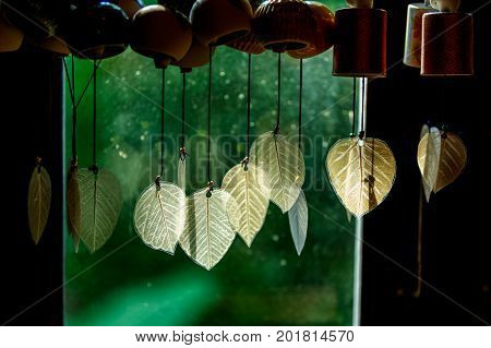 Chimes hanging in the window Decorative bells hang on the window behind with bokeh background The traditional wind bell fluttering in tropical wind in Thai house.