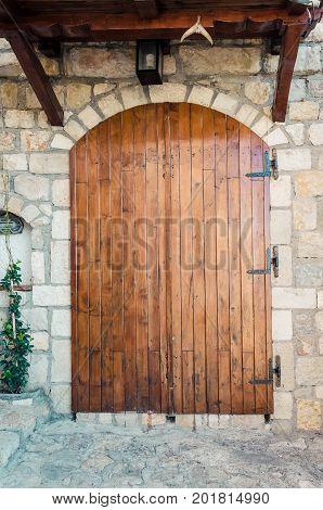 Stone wall with brown wooden door in Stari Grad of Ulcinj Montenegro.