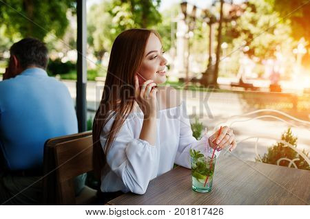 Portrait Of An Attractive Young Businesswoman Holding A Mojito Cocktail And Talking On The Phone In