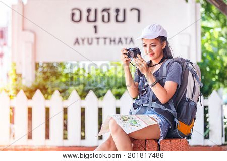 Young beautiful asian female traveler with backpack traveling and enjoying happiness with take a photo in train station at Ayutthaya Province Thailand