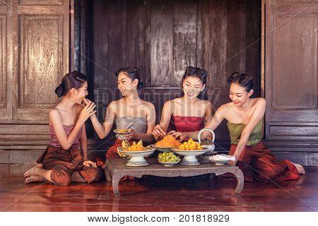 Beautiful thai girls in thai traditional costume and enjoy eating thai dessert