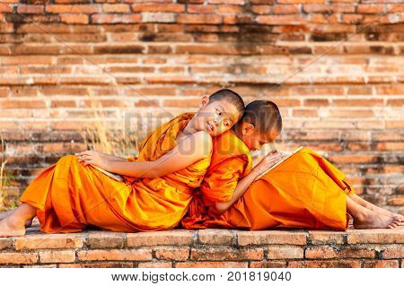 Two novice reading and studying blackboard with funny in old temple Ayutthaya Province Thailand