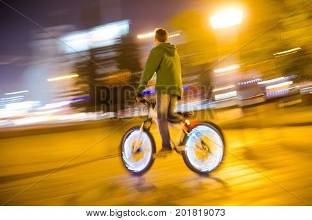 Blurred lights of the city at night and a silhouette of a cyclist with glowing wheels