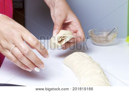 Preparation Of Cinnamon Rolls. The Woman Cuts The Workpiece Into Rolls Into Separate Rolls.