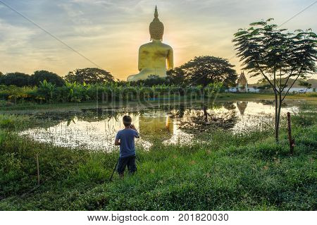 Photographer take a photo with big buddha in wat muang background at Ang Thong Province popular buddhist shrine in Thailand.