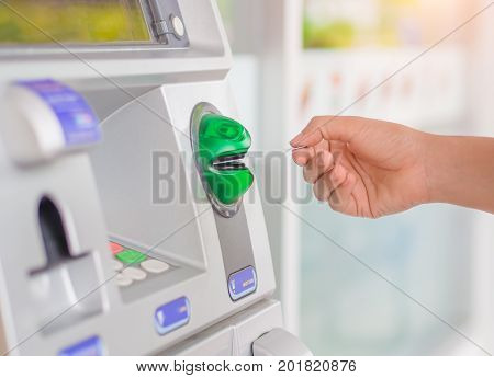 Close-up of woman's hand inserting debit card into an ATM machine.