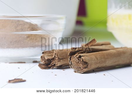 Ingredients For Making Pastry Rolls. Crushed Cinnamon And Sugar Are Mixed In A Glass Container. Near