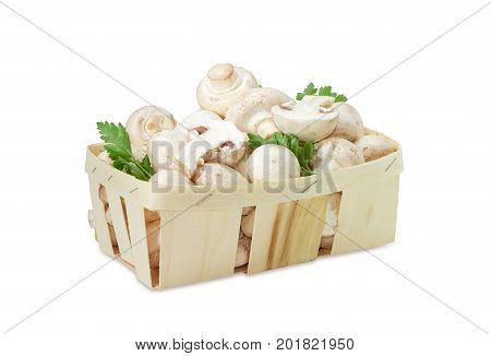 Fresh cultivated button mushrooms with twigs of parsley in the wooden basket on a white background