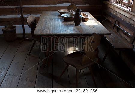 Room on the old weekend cottage. In the middle there is an oak table. On the table there is shallow flasket jug bowl and a wooden spoon. There are two chairs and settle at the table.