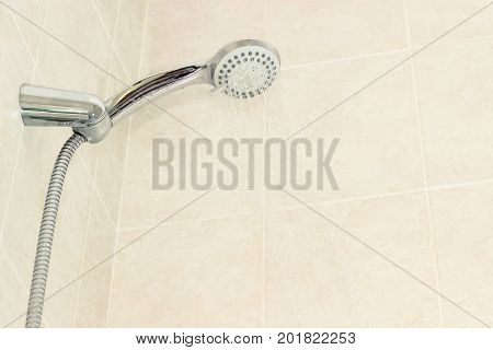 Water flowing from shower head with turn lever of a spray settings and metal shower hose in holder on a background of a wall with beige tiles