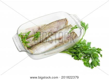 Several carcasses of the notothenia fish without of a heads and tails and with peeled scales and prepared for baking in the rectangular glass for baking and parsley on a white background